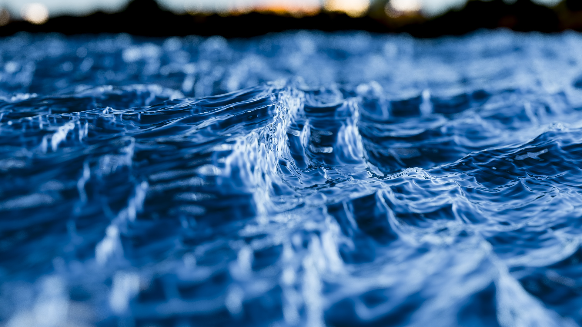 Figure 3: Another view of the vector displaced ocean surface from Figure 1. The ocean surface has a dielectric refractive material complete with colored attenuated transmission. A shallow depth of field is used to lend added realism.
